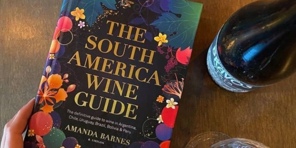 Image of The South America Wine guide book with a bottle of red wine (Image credit Vagabond Wines)