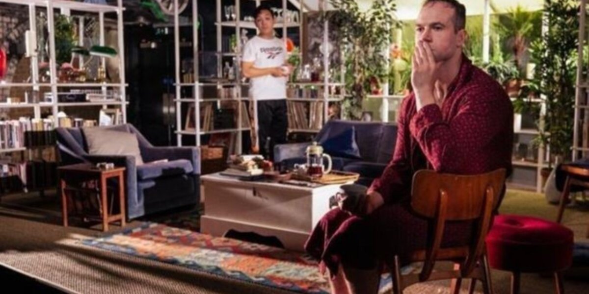 Still image of My Night with Reg, a character with his hands covering his face sitting down in living room with a character in the background holding a cup of tea.